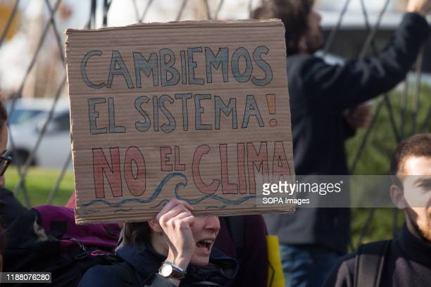 Protester holds a placard that says Let's change the system, not the climate during the demonstration. There was a spontaneous saucepan protest at...