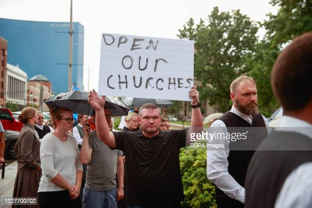 Protester holds a placard that says Open Our Churches during the We Will Not Comply anti mask rally. People protest against both the Indianapolis...