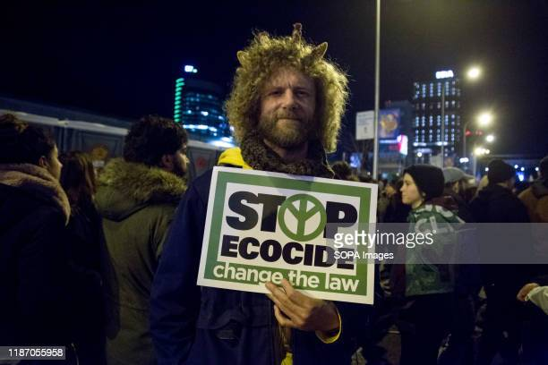 Protester holds a placard that says Stop ecocide, change the law during the demonstration. Thousands of people from all over Europe protest in Madrid...