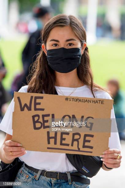 Protester holds a placard that says 'We belong here' during a Stop Asian Hate protest at Parliament Square in London. Anti-Asian violence and abuse...