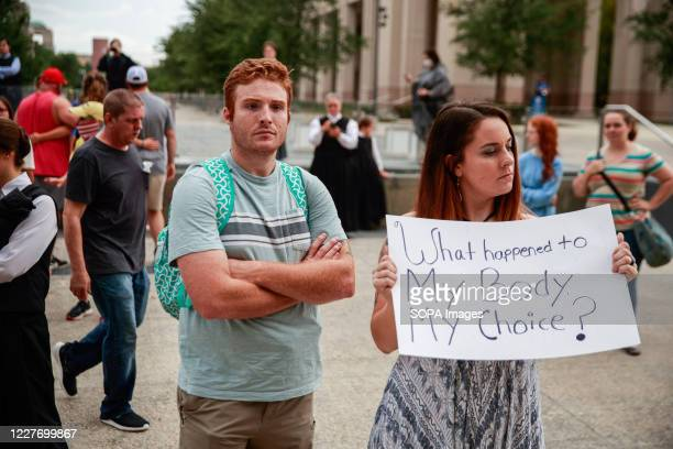Protester holds a placard that says What happened to My Body, My Choice? during the We Will Not Comply anti mask rally. People protest against both...