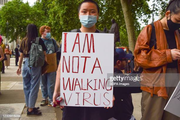 Protester holds a placard which says 'I Am Not A Walking Virus' during the Stop Asian Hate rally in Parliament Square against increasing anti-Asian...