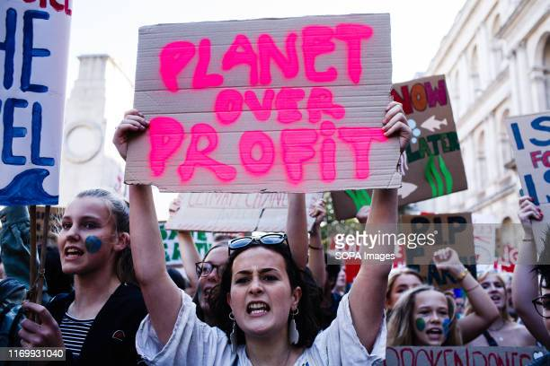 Protester holds a placard while shouting slogans during the demonstration Thousands of Environmentalists take part in the first day of a week of...