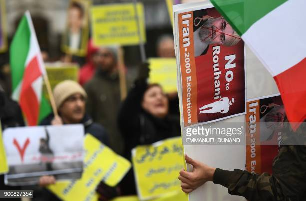 A protester holds a placard with a crossedout portrait of Iranian President Hassan Rouhani during a demonstration in support of the Iranian people...