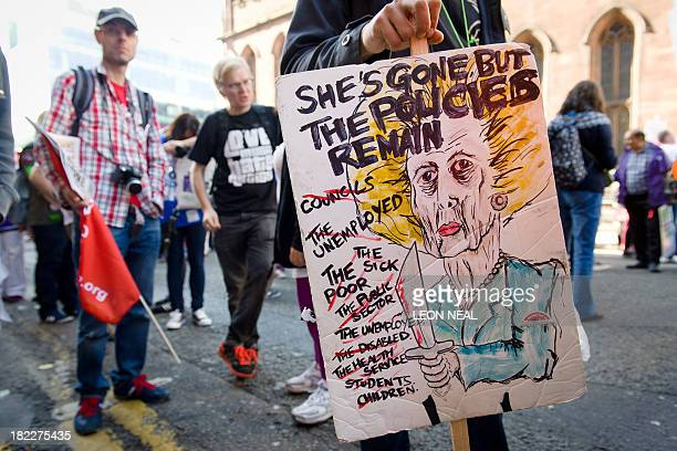 A protester holds a placard with a drawing of late British former prime minister Margaret Thatcher during a march in support of Britain's National...