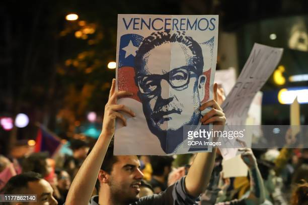 Protester holds a placard with a picture of the Chilean Ex President Salvador Allende during the no to the reform march in Montevideo. People march...