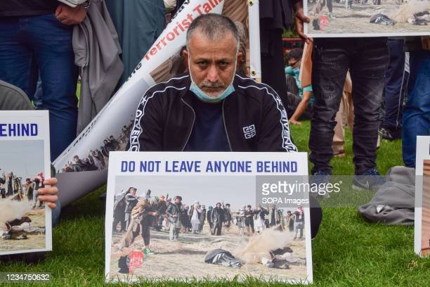 Protester holds a placard with an image of an execution and the message 'Do Not Leave Anyone Behind', during the demonstration in Parliament Square....