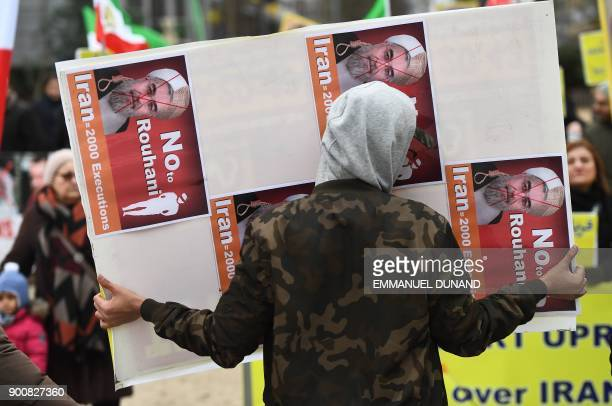 A protester holds a placard with crossedout portraits of Iranian President Hassan Rouhani during a demonstration in support of the Iranian people...