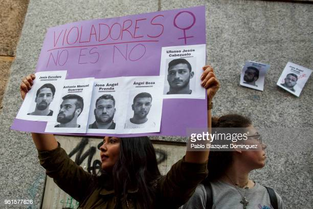 A protester holds a placard with pictures depicting the members of 'La Manada' during a demonstration against the verdict of the 'La Manada' gang...