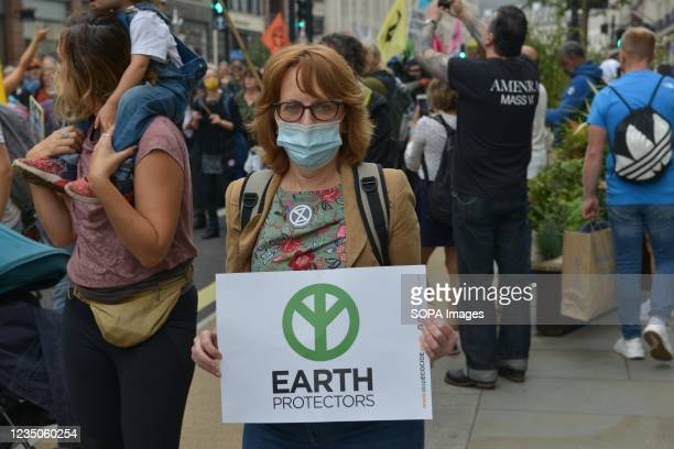"""Protester holds a placards during the demonstration. Extinction Rebellion Activists marched from Trafalgar Square to Marble Arch during the """"March..."""