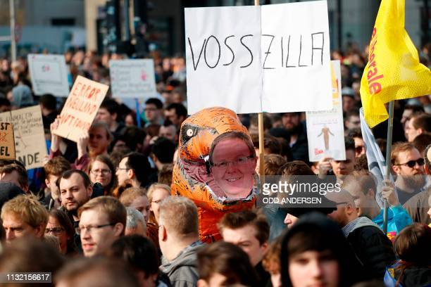 A protester holds a plastic Godzilla and a portrait of German member of European Parliament Axel Voss during a demonstration under the slogan Save...