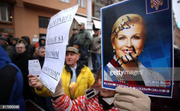 A protester holds a portrait of Croatian President Kolinda GrabarKitarovic with insults written on it during a protest by widows of the soldiers of...
