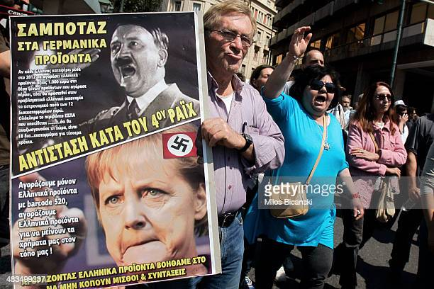 A protester holds a poster comparing Adolf Hitler and Angela Merkel as they march towards Parliament duringa labour strike on April 9 2014 in Athens...