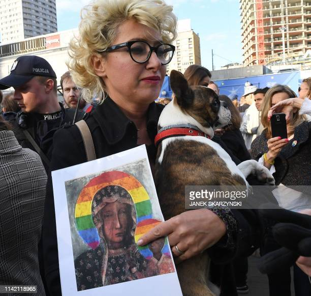 A protester holds a poster depicting the Virgin Mary with a rainbow halo during a rally for freedom of speech in downtown Warsaw on May 7 2019 after...