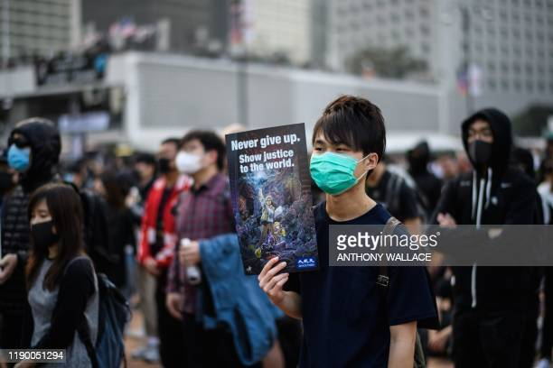 TOPSHOT A protester holds a poster during a rally in Hong Kong on December 22 2019 to show support for the Uighur minority in China Hong Kong riot...