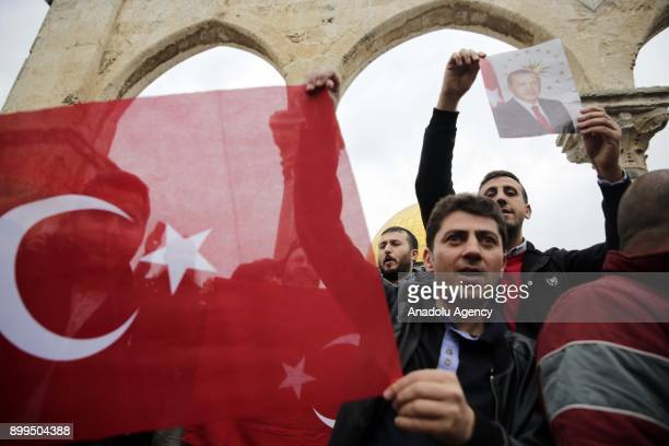 A protester holds a poster of Turkish President Recep Tayyip Erdogan during a demonstration against US President Donald Trumps announcement to...