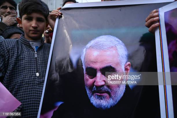 A protester holds a poster with the image of top Iranian commander Qasem Soleimani who was killed in a US airstrike in Iraq in the Kashmiri town of...