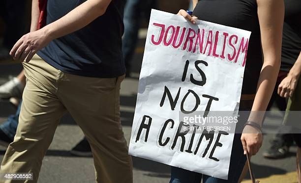 FILES Protester holds a poster written 'Journalism in not a crime' during a demonstration in support of freedom of press on August 1 in Berlin as...