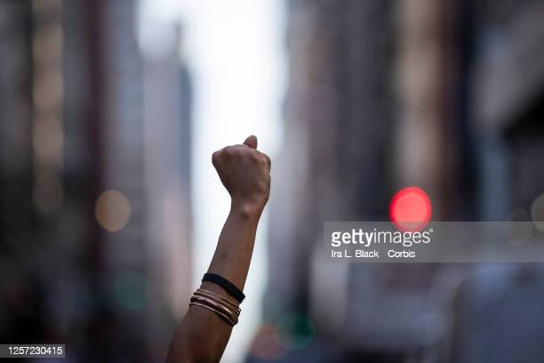 A protester holds a raised black power fist in between the buildings as they marched from Union Square to City Hall in Manhattan This was the day...