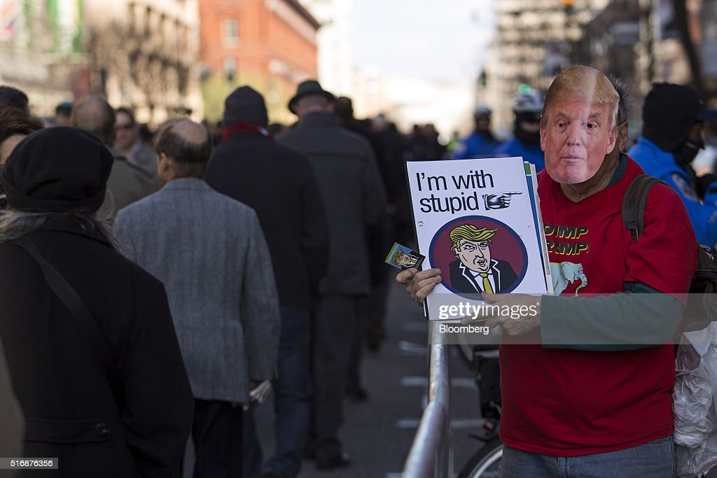 A protester holds a sign and wears a mask in the likeness of Donald Trump, president and chief executive of Trump Organization Inc. and 2016 Republican presidential candidate, outside the American Israeli Public Affairs Committee (AIPAC) policy conference in Washington, D.C., U.S., on Monday, March 21, 2016. The presidential race will take a detour from domestic sniping today as Hillary Clinton, Donald Trump and Trump's two Republican opponents converge on Washington to address a key pro-Israel group. Photographer: Drew Angerer/Bloomberg via Getty Images