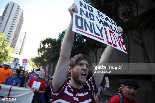 A protester holds a sign as he marches during a May Day demonstration on May 1 2017 in San Francisco California Thousands are expected to take to the...