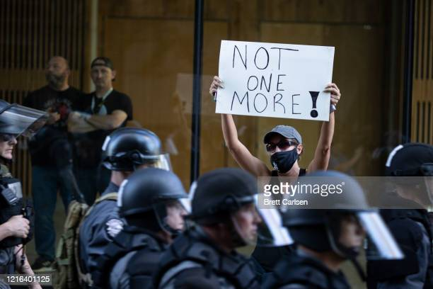 Protester holds a sign as police in riot gear move down the street in formation on May 30, 2020 in Louisville, Kentucky. Protests have erupted after...