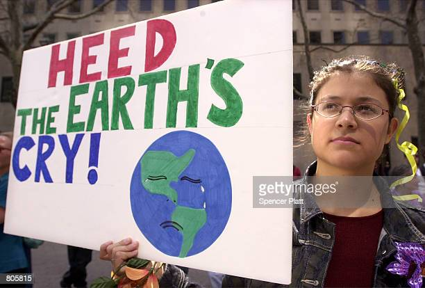 A protester holds a sign at an Earth Day rally April 22 2001 in front of the United Nations in New York City Dozens of activists marched from Times...