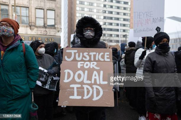 Protester holds a sign calling for justice for Dolal Idd, who was shot and killed by Minneapolis Police during a sting operation in December 2020, on...