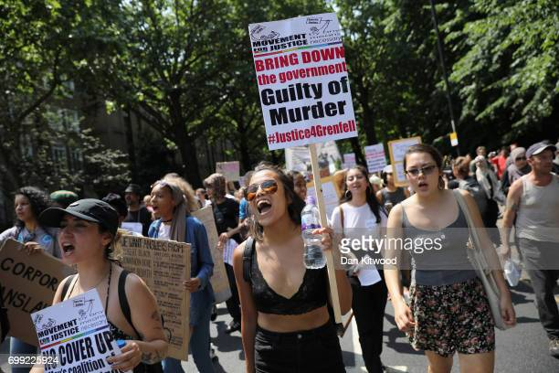 A protester holds a sign calling for justice for the victims of the Grenfell Disaster as they march towards Westminster during an antigovernment...