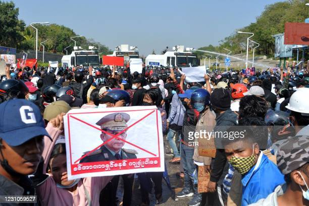 Protester holds a sign denouncing Myanmar military chief General Min Aung Hlaing as police fire a water cannon during a demonstration against the...