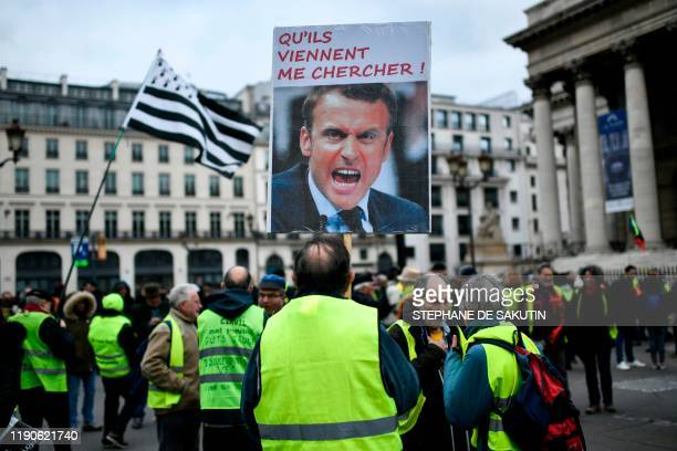 """Protester holds a sign depicting French President and reading """"Let them come and get me !"""" on the Place de la Bourse in Paris during a demonstration..."""
