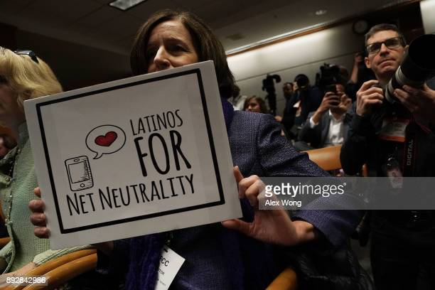 A protester holds a sign during a Federal Communications Commission meeting December 14 2017 in Washington DC FCC has voted to repeal its net...