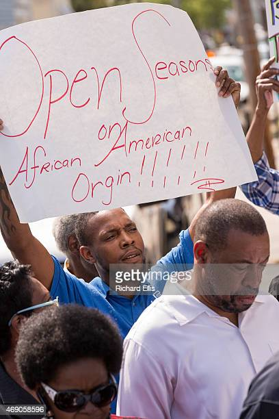 A protester holds a sign during a press conference by the President of the Charleston Chapter of the NAACP Dot Scott to discuss the police killing of...