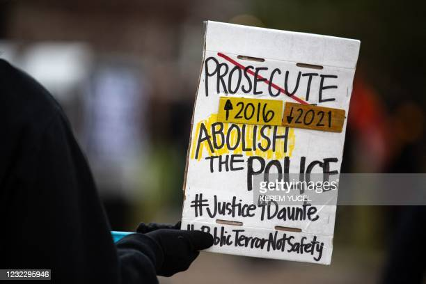 Protester holds a sign during a protest where Daunte Wright was shot and killed by a police officer in Brooklyn Center, Minnesota on April 13, 2021....