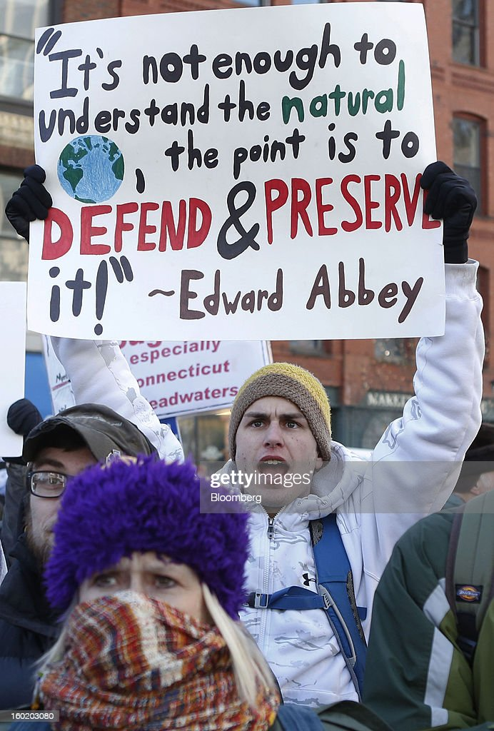 A protester holds a sign during a rally against the possibility of so-called tar sands oil being piped in from Montreal, in Portland, Maine, U.S., on Saturday, Jan. 26, 2013. The Associated Press reported that environmental groups say plans are in the works to bring oil by pipeline from western Canada to Montreal and then to Portland. Critics say tar sands, or oil sands, oil is so corrosive, acidic and thick that it's more likely to spill than conventional crude oil and that would put rivers, lakes and streams at risk in Maine, New Hampshire and Vermont, according to AP. Photographer: Bizuayehu Tesfaye/Bloomberg via Getty Images