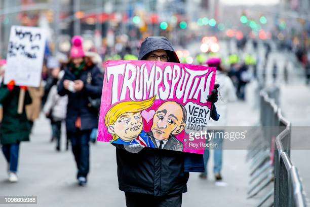 A protester holds a sign featuring US President Donald Trump and Russian President Vladimir Putin during the 2019 Women's March on January 19 2019 in...