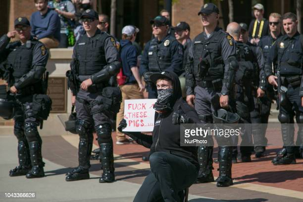 A protester holds a sign in front of police during an open carry rally at Kent State University in Kent Ohio on September 29 2018