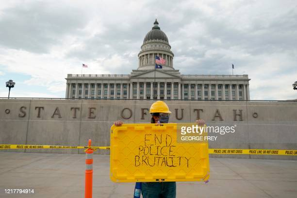 Protester holds a sign in front of the Utah State Capitol building during a protest in Salt Lake City, Utah on June 5, 2020. - A couple thousand...