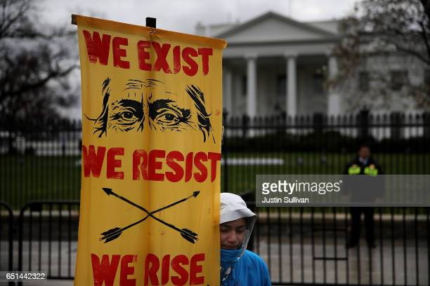 A protester holds a sign in front of the White House during a demonstration against the Dakota Access Pipeline on March 10 2017 in Washington DC...