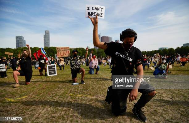 A protester holds a sign in protest as people gather on Malieveld in The Hague to attend a solidarity rally against racism in the aftermath of the...