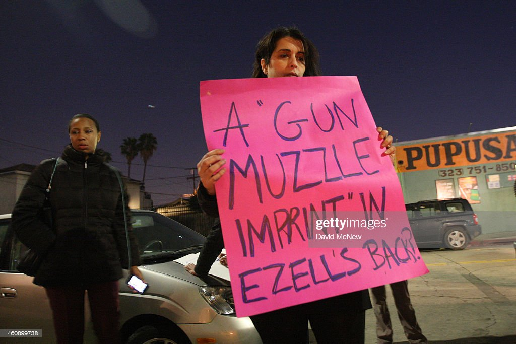 A protester holds a sign near the site where Ezell Ford, a 25-year-old mentally ill black man, was shot and killed by two LAPD officers in August, on December 29, 2014 in Los Angeles, California. The long-awaited autopsy report, which was put on a security hold at the request of police and ordered by L.A. Mayor Eric Garcetti to be made public before the end of 2014, was released December 29.