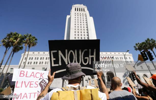 A protester holds a sign outside City Hall reading 'Enough' during a peaceful demonstration over George Floyd's death on June 3 2020 in Los Angeles...