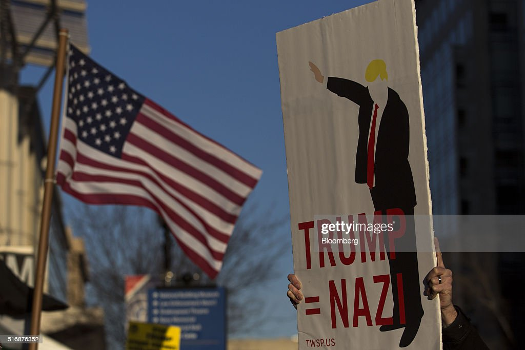 A protester holds a sign outside the American Israeli Public Affairs Committee (AIPAC) policy conference in Washington, D.C., U.S., on Monday, March 21, 2016. The presidential race will take a detour from domestic sniping today as Hillary Clinton, Donald Trump and Trump's two Republican opponents converge on Washington to address a key pro-Israel group. Photographer: Drew Angerer/Bloomberg via Getty Images