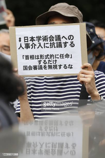 Protester holds a sign outside the prime minister's office in Tokyo on Oct. 3 criticizing Japanese Prime Minister Yoshihide Suga's decision not to...