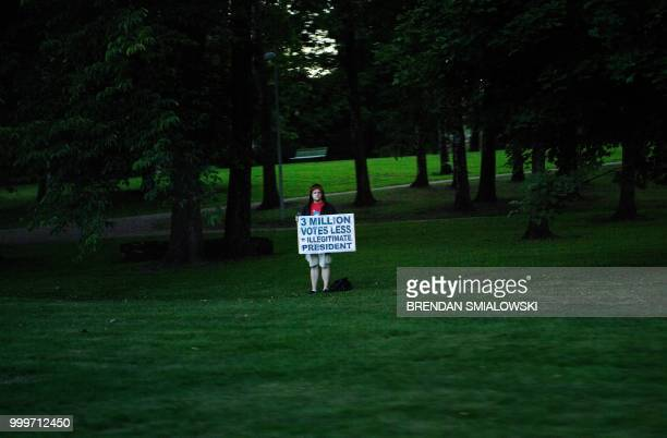 """Protester holds a sign reading """"3 millions votes less = illegitimate President"""" while watching as a motorcade with US President Donald Trump and US..."""