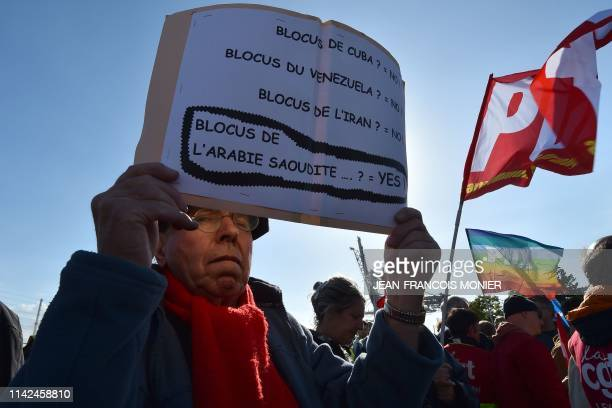 A protester holds a sign reading blockade of Cuba No blockade of Venezuela No Blockade of Iran No Blockade of Saudi Arabia Yes during a demonstration...