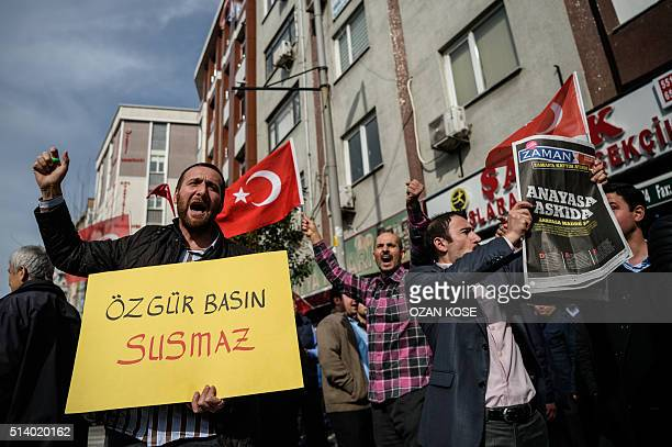 A protester holds a sign reading 'Free media can not be silenced' during a demonstration near the headquarters of the newspaper Zaman in Istanbul on...