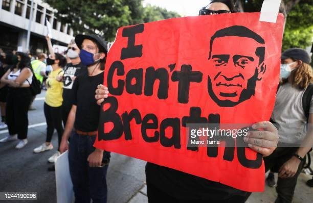 A protester holds a sign reading 'I Can't Breathe' outside the District Attorney's office during a peaceful demonstration over George Floyd's death...