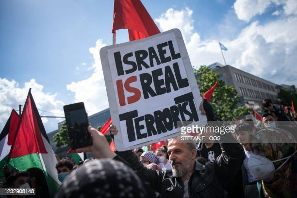 """Protester holds a sign reading """"Israel is real terrorist"""" as he takes part in a demonstration in solidarity with the Palestinians called over the..."""