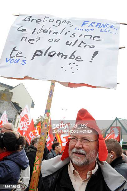 A protester holds a sign reading Neoliberalism or ultraliberalism kills you during a demonstration organised by unions against job losses in Brittany...